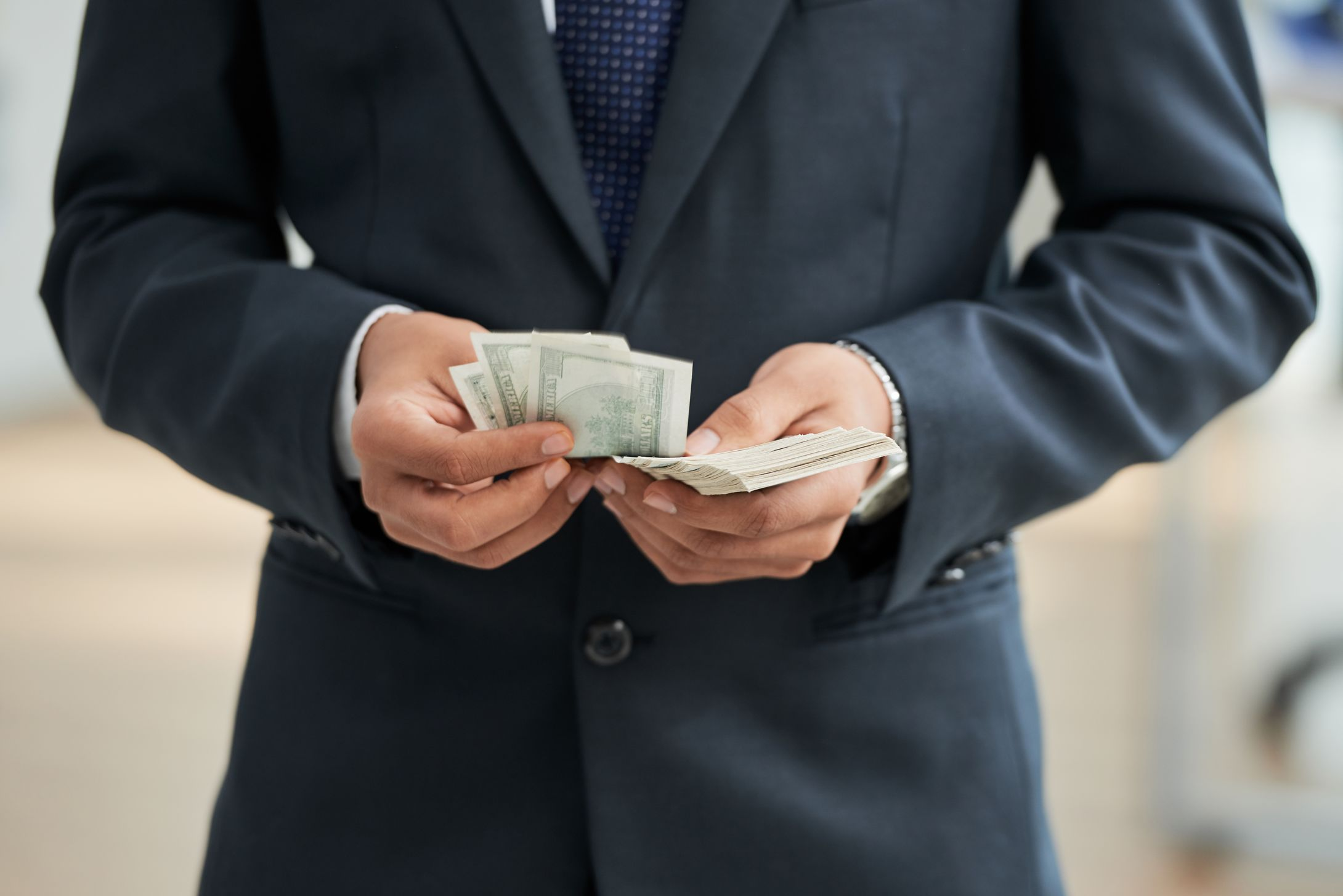 Close-up of businessman in black suit counting dollar currencies